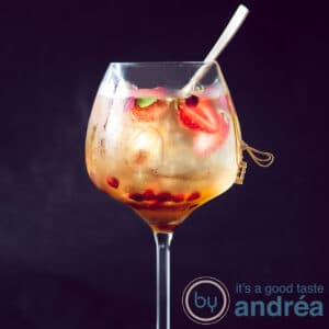 A gin glass filled with Sangria Blanca 43 and a golden spoon inside. A black background