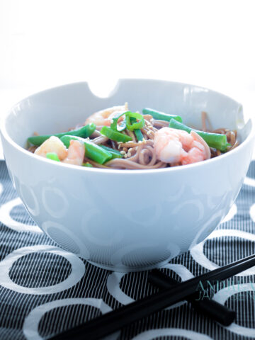 a bowl with noodles, shrimp and green beans