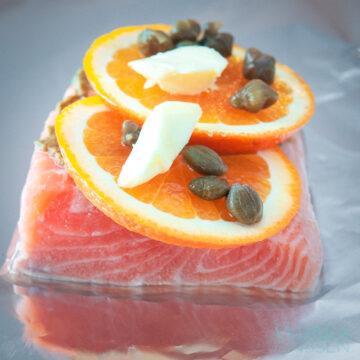 aluminium foil with salmon, orange slices, butter and capers on top.
