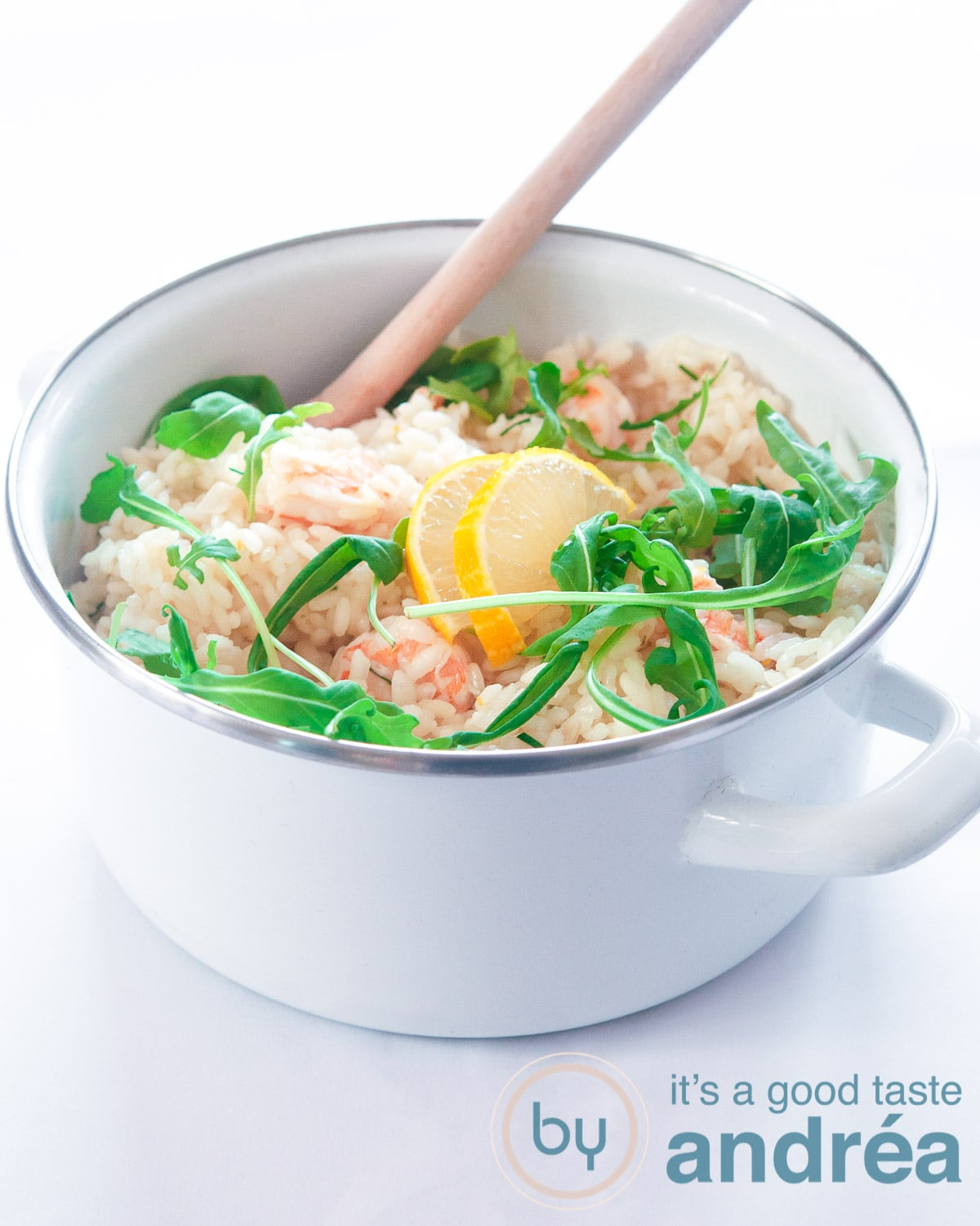 A white pan with risotto with shrimp and arugula