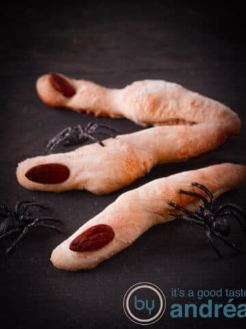 3 creepy bread fingers with spiders on a wooden board