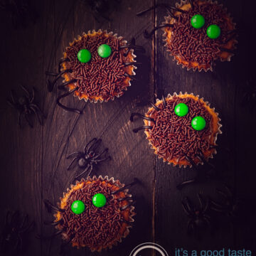 4 Halloween cupcakes with sprinkles and M&M's and some spiders