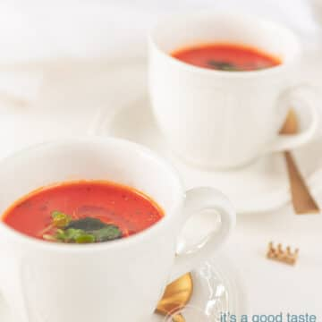 two cups with Rich tomato soup and golden spoons