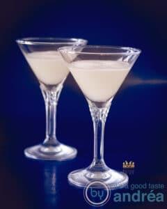 Twee kristallen glazen gevuld met sour sherry cream op een blauwe achtergrond.