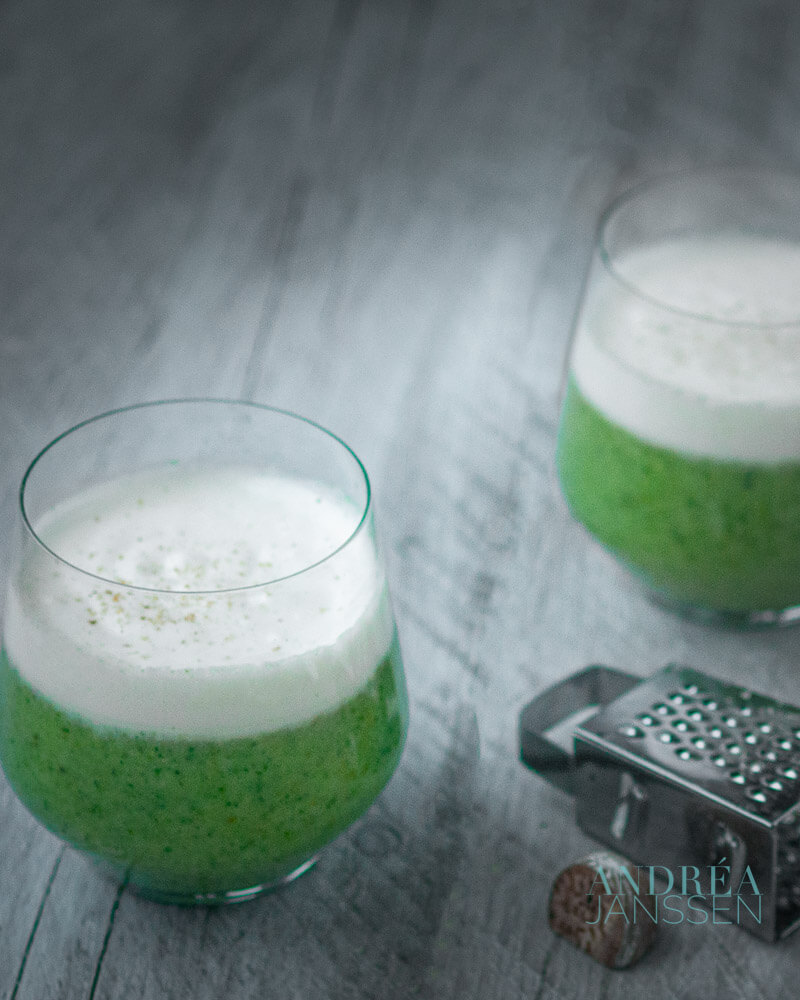 two glasses broccoli soup with a cream topping and some nutmeg