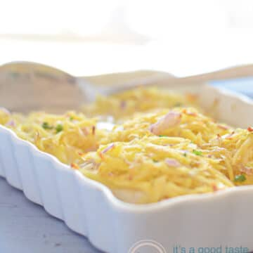 a white casserole dish on a blue background filled with cod fillets topped with potato gratin