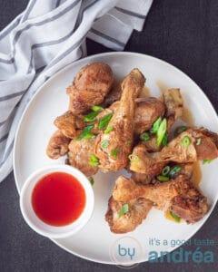 een bord met kip drumsticks in soja saus en een kommetje met chilisaus