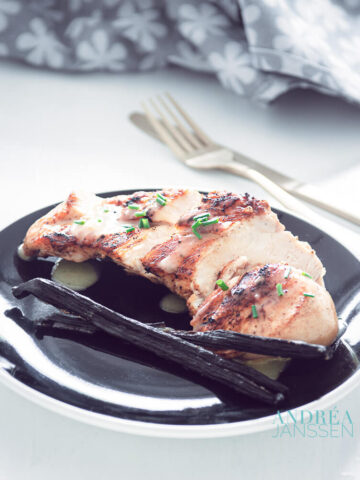 Chicken with vanilla sauce on a black plate