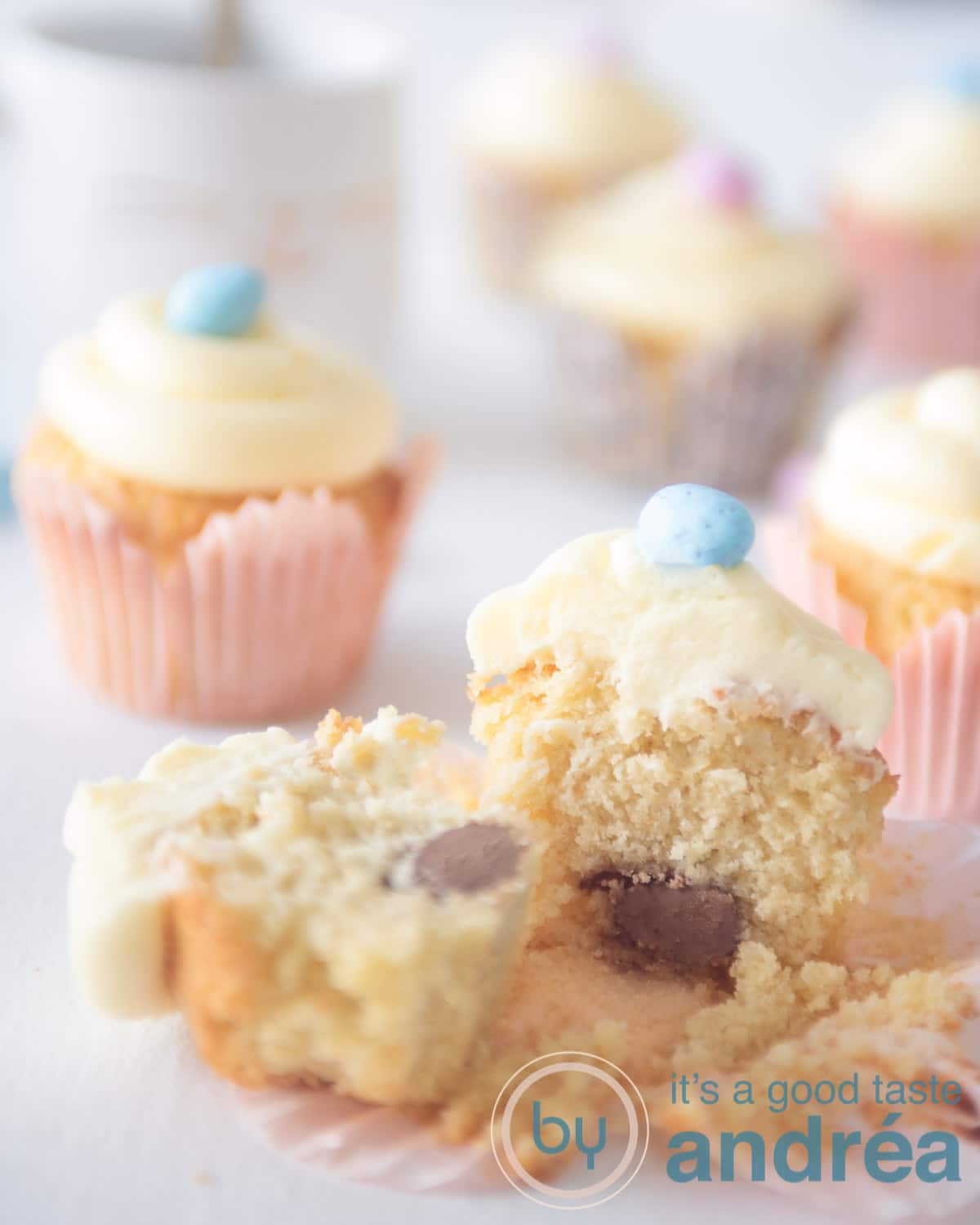 a bunch of easter cupcakes on a white background. One cupcake is halved and you can see a chocolate egg.