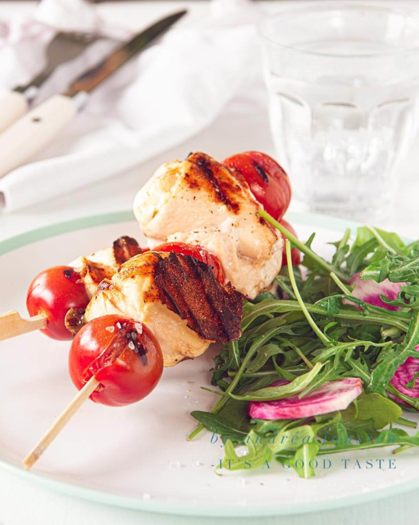 a plate with two skewers of chicken mozzarella kebabs and a salad