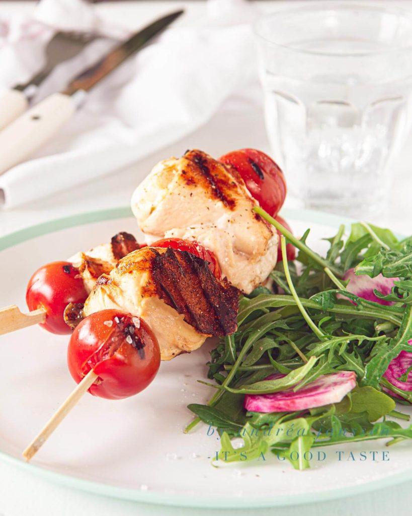 een bord met twee kip mozzarella spiesjes een een salade