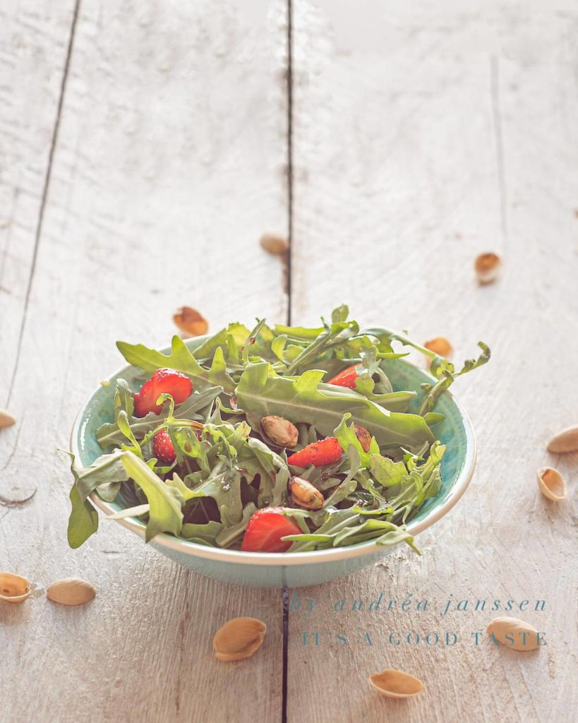 A bowl with Strawberry, arugula and pistachio salad