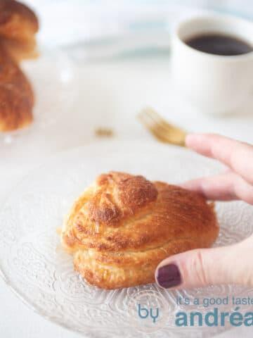 Een hand die een Zeeuwse bolus vastpakt. Dit zoete broodje ligt op een glazen bord.