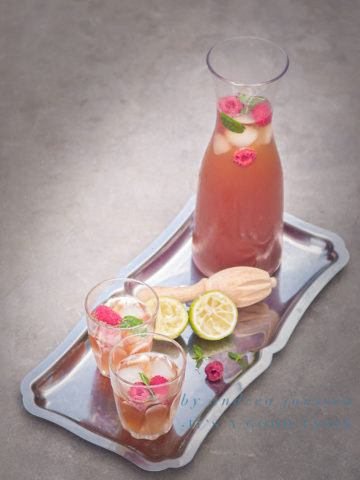 A jar of Lime rose ice tea with raspberries and two glasses filled with ice tea