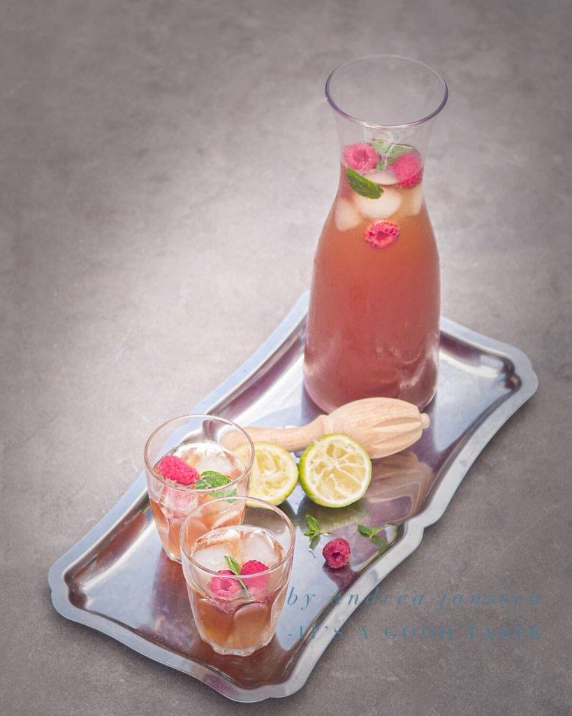 een dienblad met een karaf Limoen rozen ijsthee met verse frambozen en twee glazen