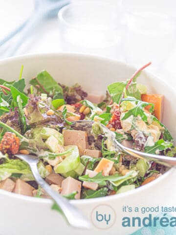 A white bowl with Smoked chicken, salad, cucumber, pine nuts and with pesto
