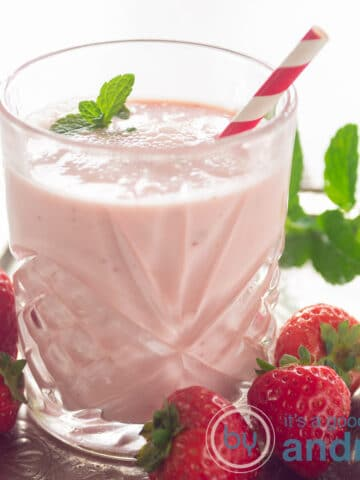 square photo with a glass filled with a strawberry orange yogurt smoothie, a red straw and surrounded with fresh strawberries and mint