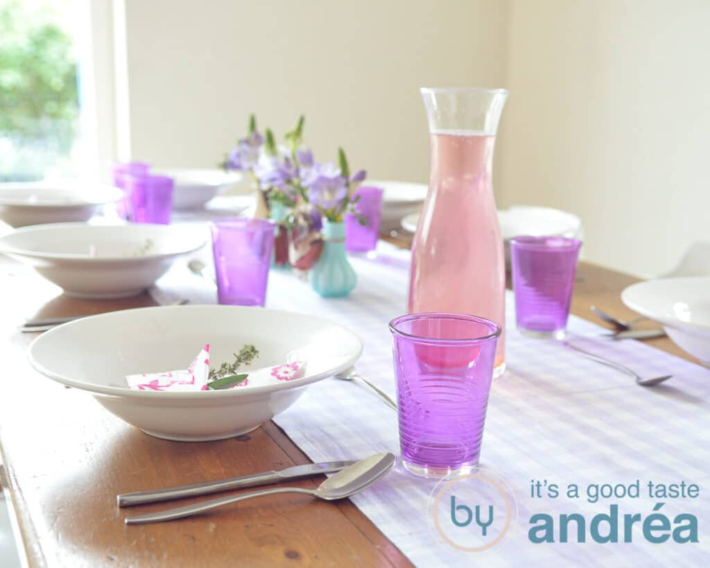 a table with pink and purple tableware