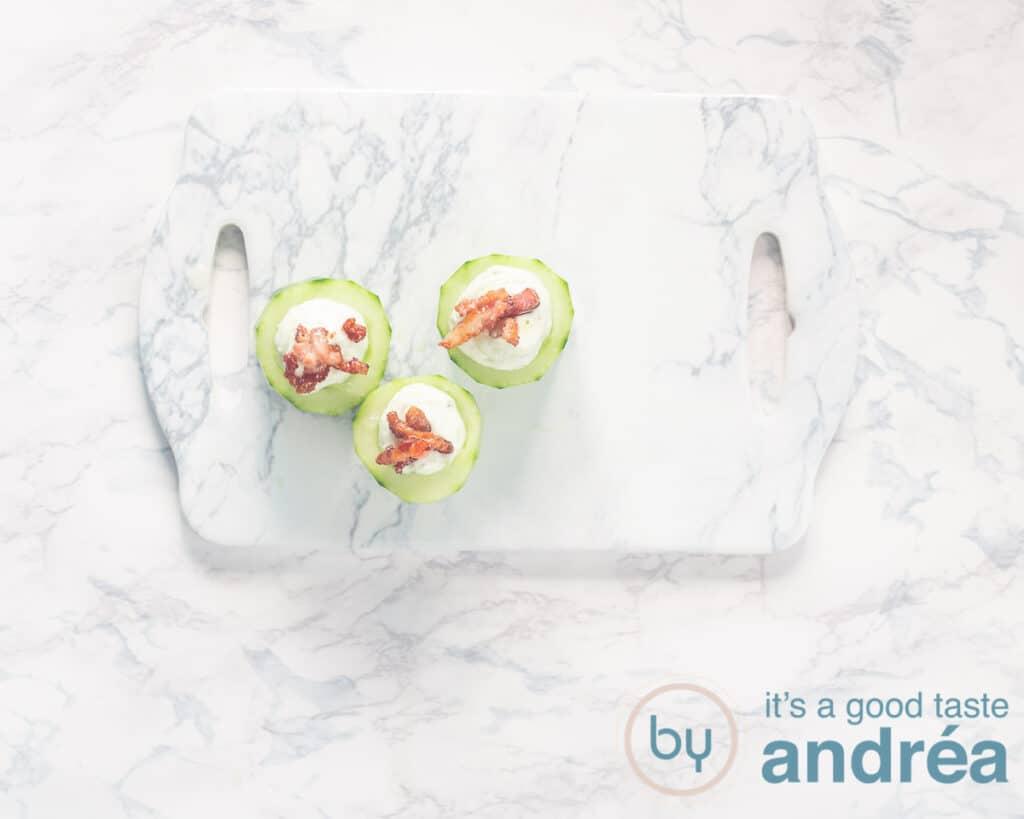 3 komkommers op snijplank gevuld met Heksenkaas en bacon