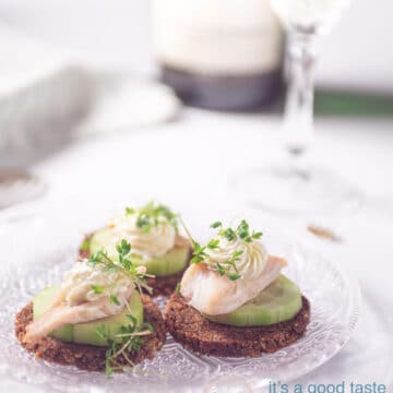 three smoked trout snacks with cucumber and rye bread on a glass plate