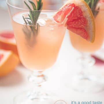 A glass filled with a rosemary grapefruit mocktail. Garnished with rosemary and slices grapefruit
