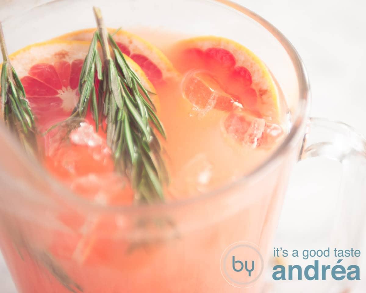 Een kan met rozemarijn grapefruit cocktail gegarneerd met rozemarijn ijsblokjes en grapefruit