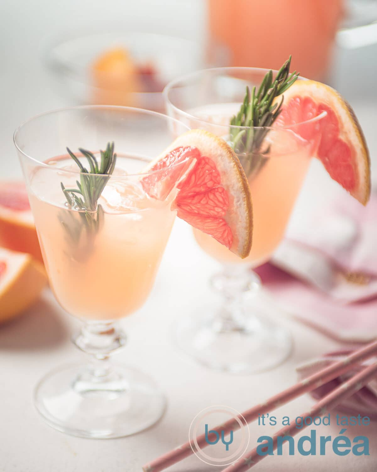 Two grapefruit mocktails with rosemary and straws