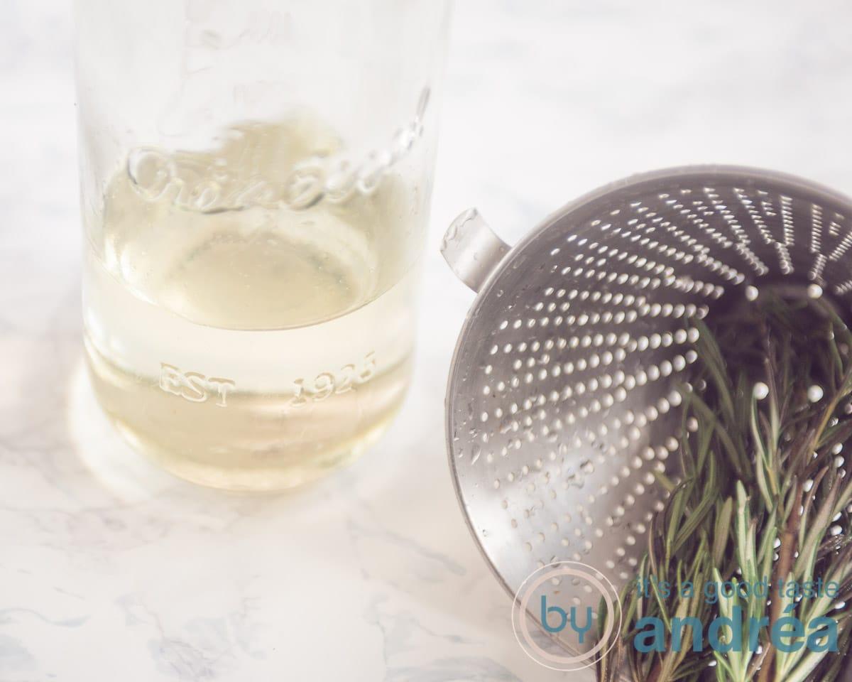 Een zeef met rozemarijn en een fles met rozemarijn siroop