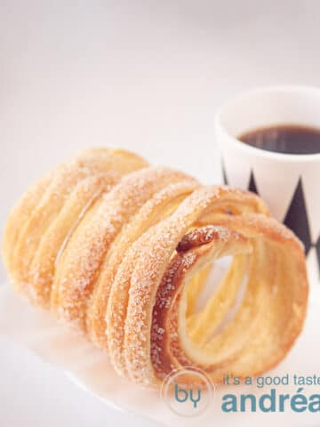 A chimney cake with a cup of coffee (in a white with black mug)