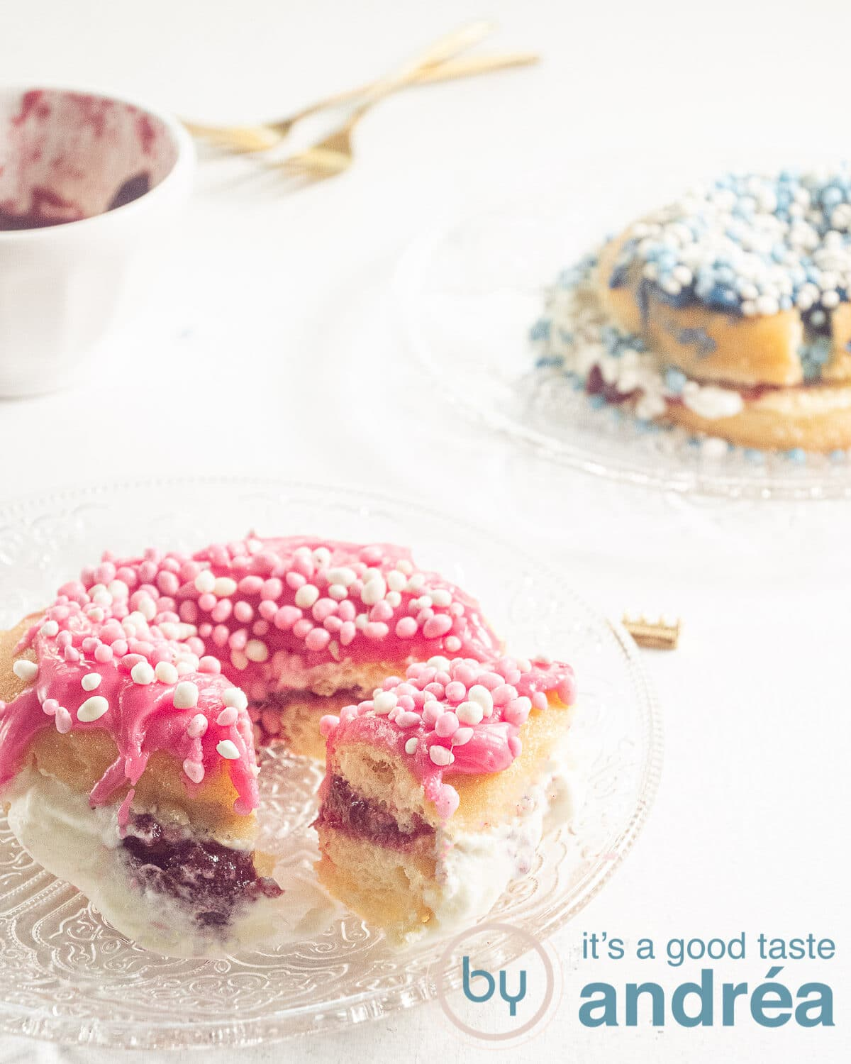two donuts on glas plates, pink and blue and some jelly
