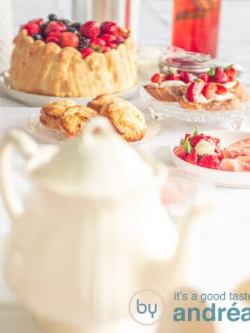 a white teapot in front and in the back high tea dishes like a Charlotte with fruit, bruschetta and strawberry lemonade
