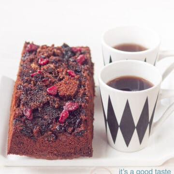 Cake with a caramelized cranberry topping on a white plate and two cups of coffee
