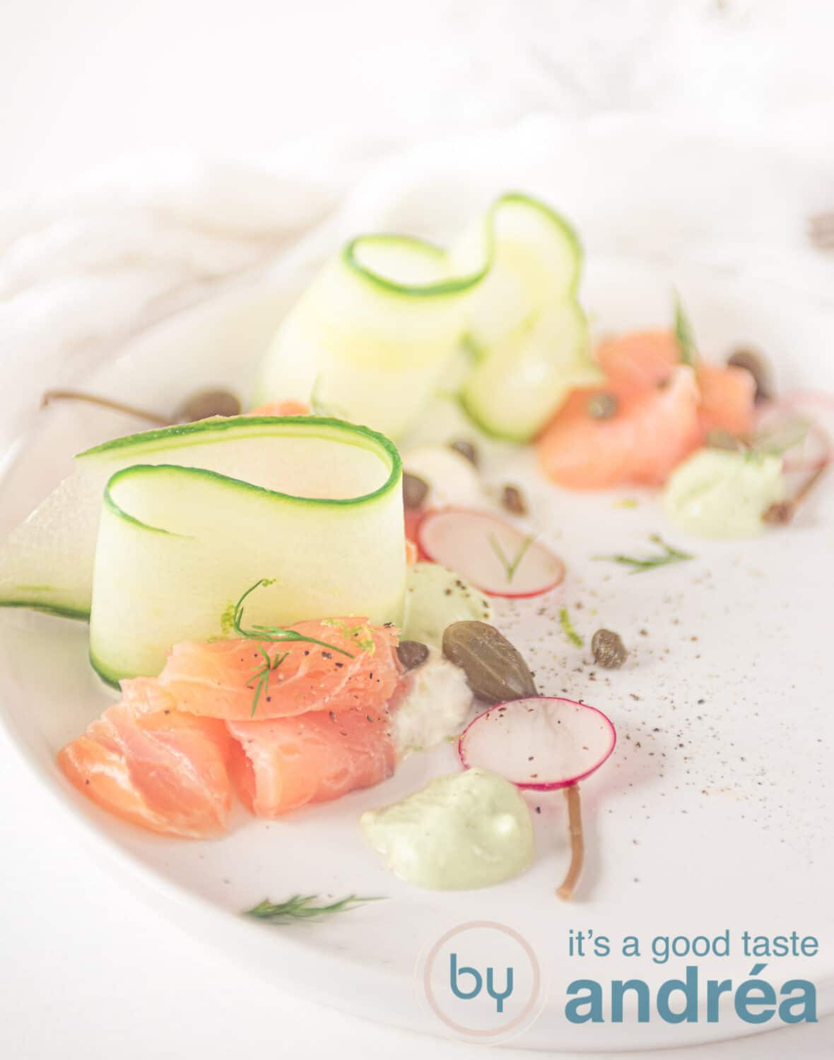 A white plate with cucumber ribbons, smoked salmon and pipings of horseradish and avocado cream