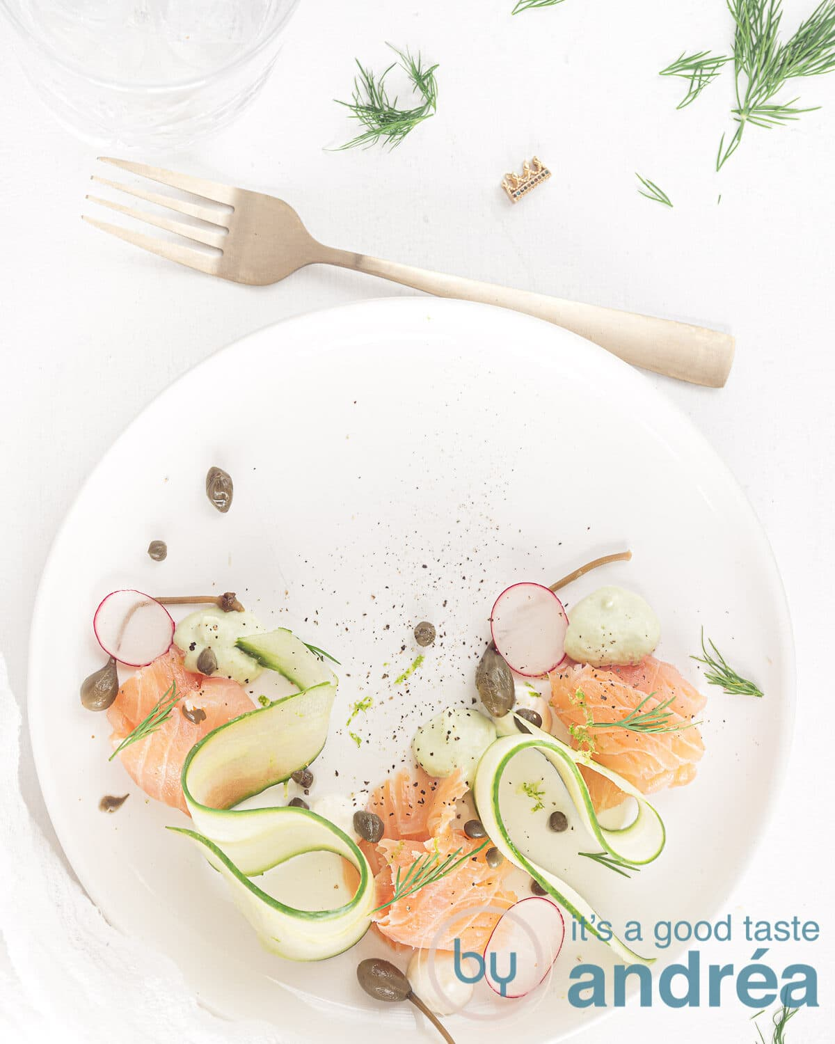 a plate with smoked salmon, cucumber ribbons and two creams a fork and some dill spread around