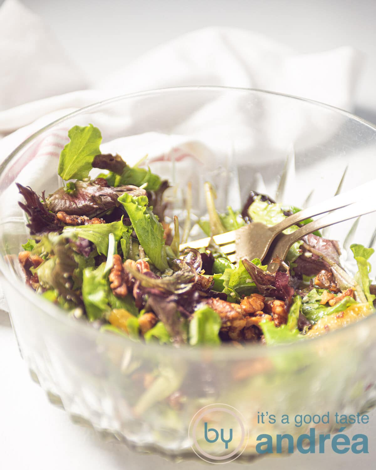 a glass bowl filled with a salad with oranges, walnuts, and blue cheese