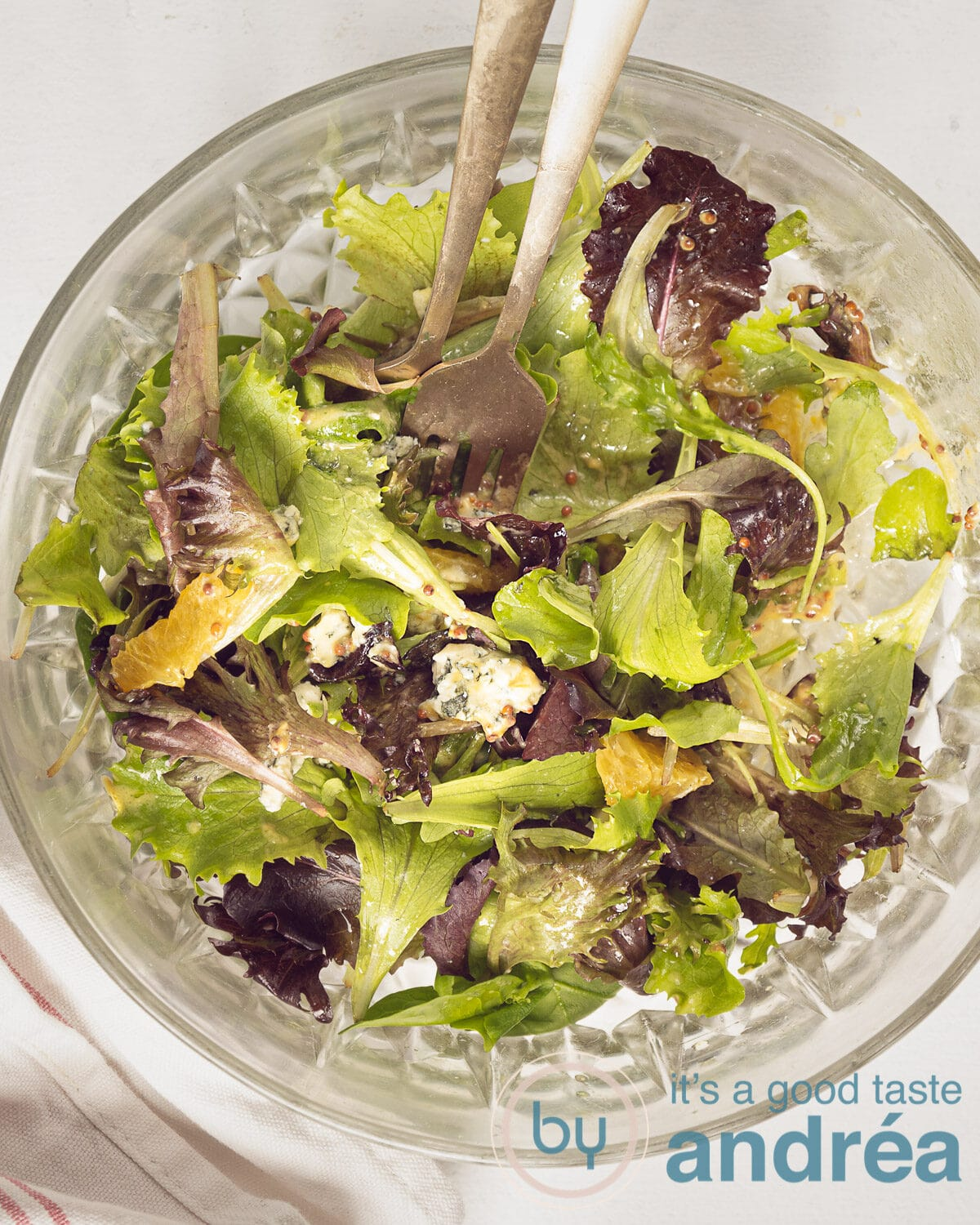 a top photo of a glass bowl, two gold forks and a mixed salad with orange, blue cheese and walnuts