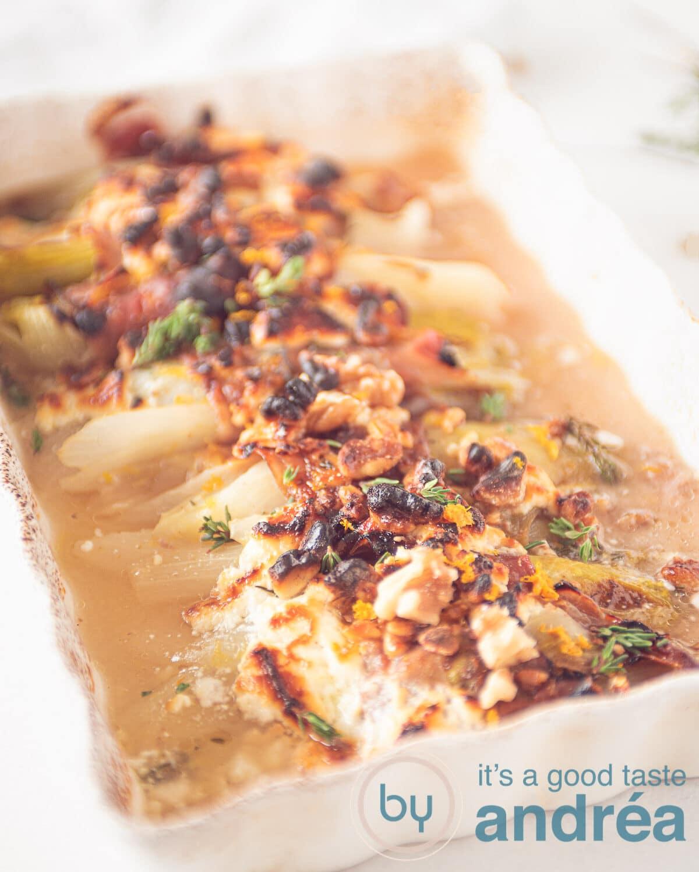een ovenschaal gevuld met halve stronken witlof omwikkelt met prosciutto, honing, geitenkaas en tijm