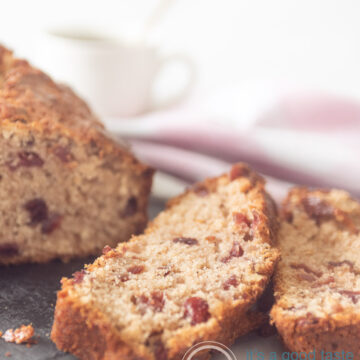 a cranberry walnut coffee cake on a silver platter. Two slices cut off.