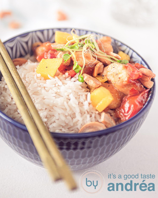 een kom met rijst en honingkip, mango en cashew noten