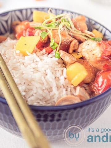 een blauwe kom met rijst, honingkip, mango, tomaat en cashewnoten