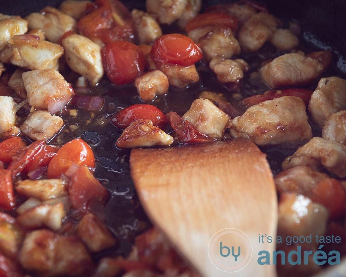 een pan met tomaten kip en specerijen