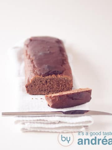 an ontbijtkoek cake on a cloth with one slice cut off