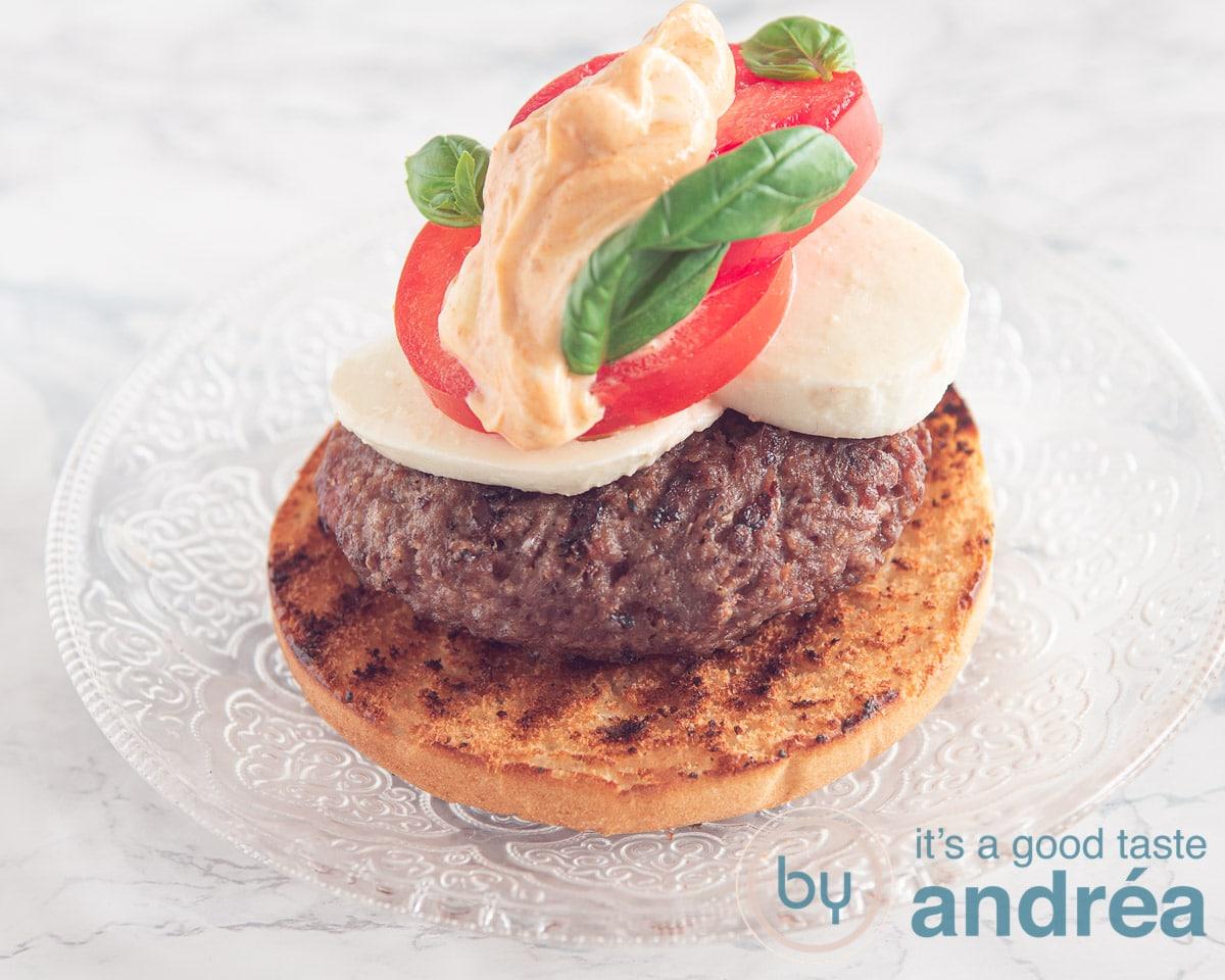a bun topped with a grilled burger, mozzarella slices, tomato and mayonaise pesto