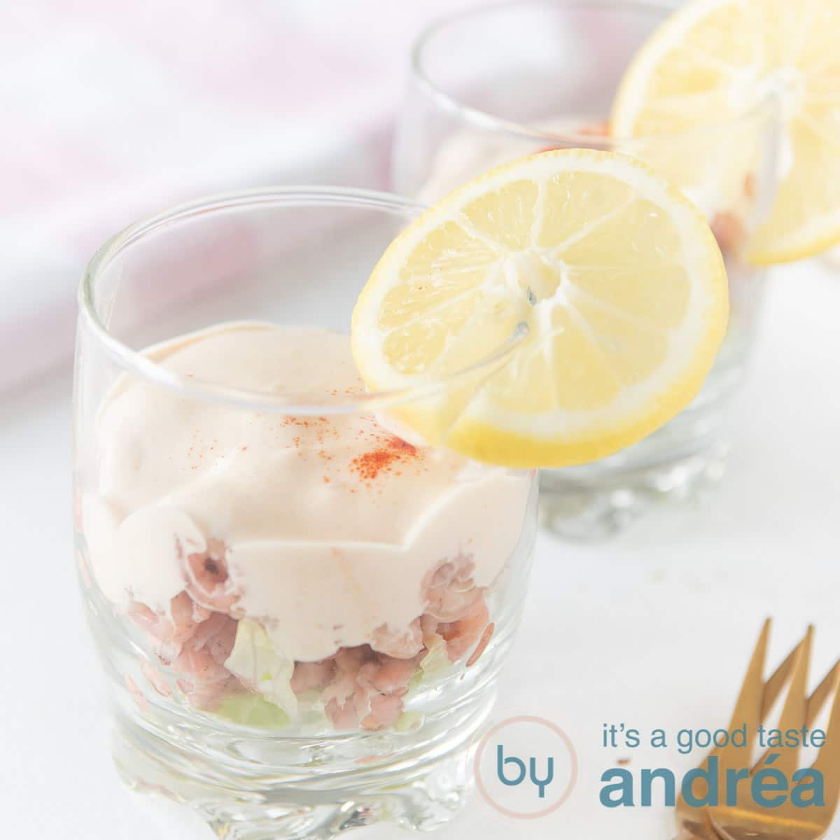 a glass filled with shrimp ice berg lettuce and sauce.