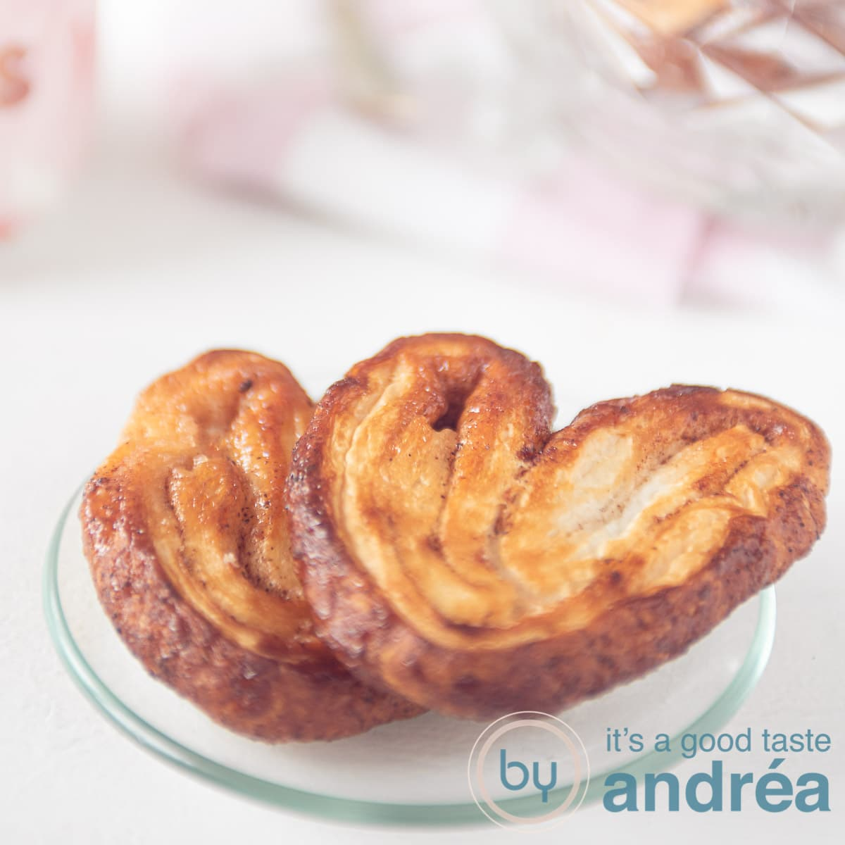 two palmier cookies on a glass plate a square photo