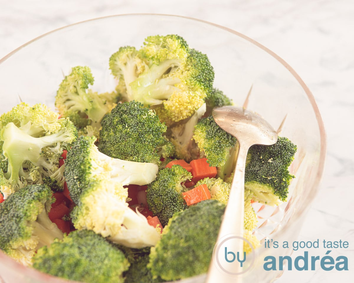 A bowl with roasted vegetables, broccoli, carrot and onions