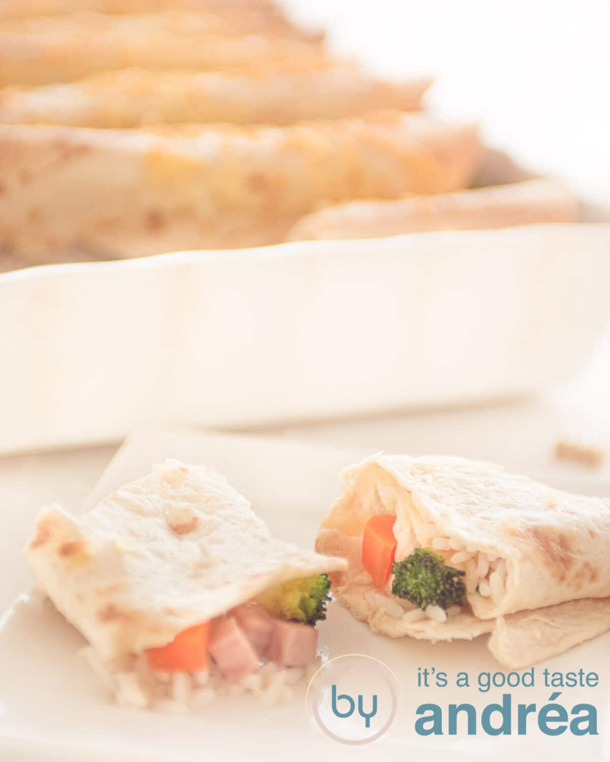 Two half wraps filled with rice, carrots, broccoli and ham and a casserole in the background