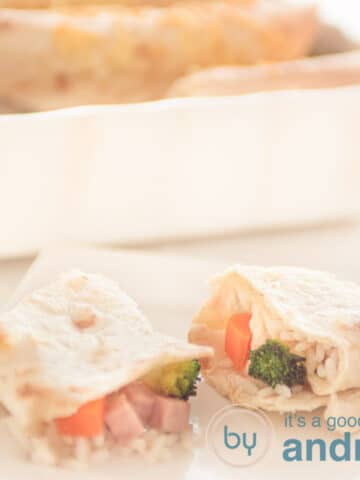 a square photo with two wraps filled with carrot, broccoli, ham and rice and a casserole in the background