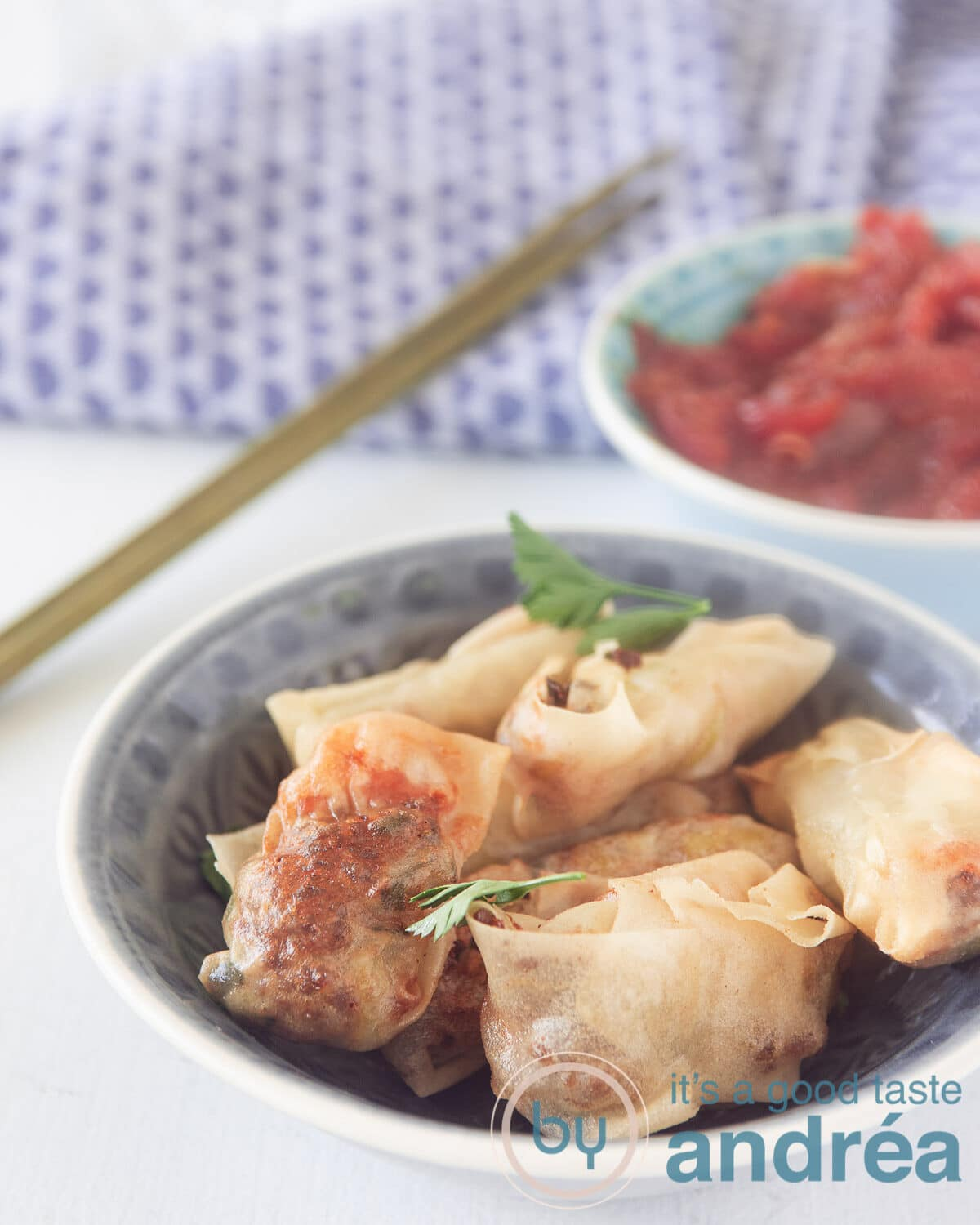 A bowl with Indonesian mini spring rolls and a bowl with a homemade sauce in the back