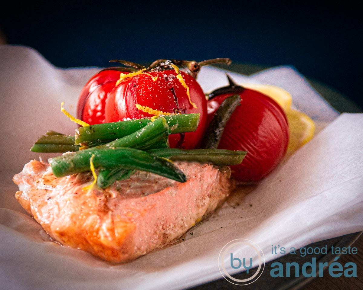 zalm op een wit bakpapiertje met asperges en tomaat